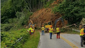 State Department of Transportation employees work Tuesday on the edge of a large mudslide covering part of N.C. 9 in Bat Cave.