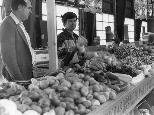 WNC Farmers Market manager Clayton Davis advises seller Donald Hensley on his display in the retail building in 1987.