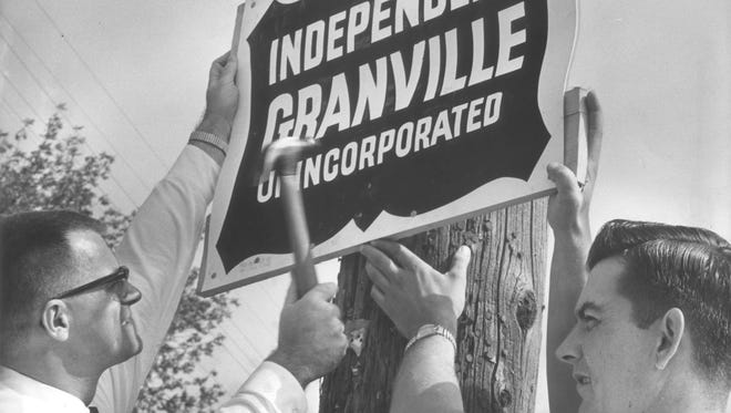 """Donald Kullmann (left) and Robert Feehery nail a sign announcing the """"independent"""" community of Granville at the corner of N. 53rd St. and W. Good Hope Road on June 17, 1962. This photo was published in the June 18, 1962, Milwaukee Journal."""