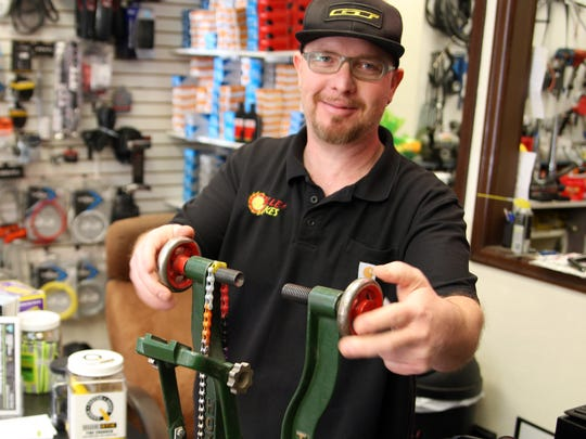 Kenny Trammel demonstrates an antique bicycle truing wheel at Valley Bikes on W. Alisal