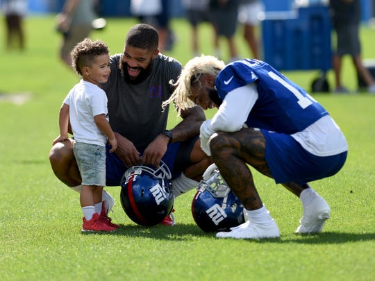 NY Giants Odell Beckham Jr. shakes his hair to make Jacolby James Latimer 2 and his father Cody Latimer #12 laugh after practice, during the first full day of of training camp at Quest Diagnostics Training Center located on the MetLife Sports Complex on July 26, 2018.