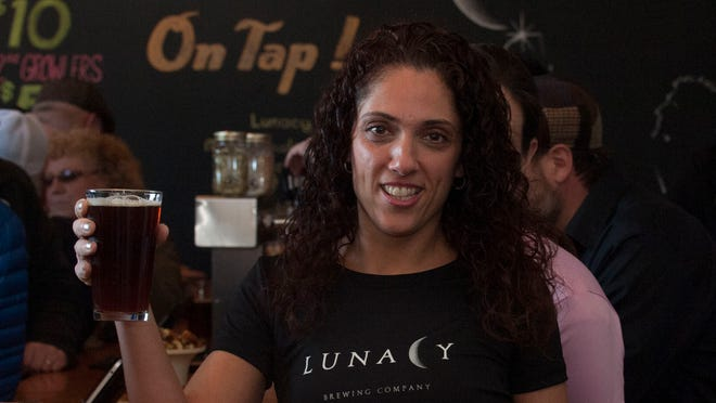 Joanna Sinclair shows an IPA beer sold at the new Brewery Lunacy Brewing in Magnolia.