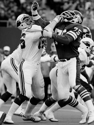 Conrad Dobler, left, of the St. Louis Cardinals, tries to block a charging George Martin of the New York Giants during the fourth period of the game at Giants Stadium, Dec. 5, 1977.