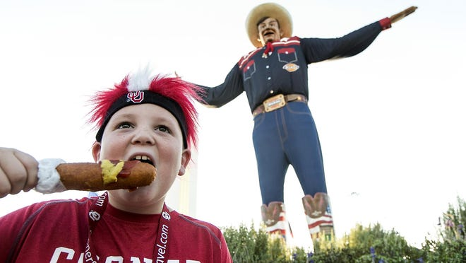 Oklahoma Sooners fan Carson Klucevsek of Chouteau, Oklahoma, enjoys a famous Fletcher's corn dog at the State Fair of Texas before the Red River Rivalry game on Saturday, Oct. 10, 2015, in Dallas.