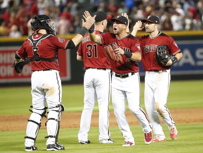 Arizona Diamondbacks catcher Alex Avila (left) slaps