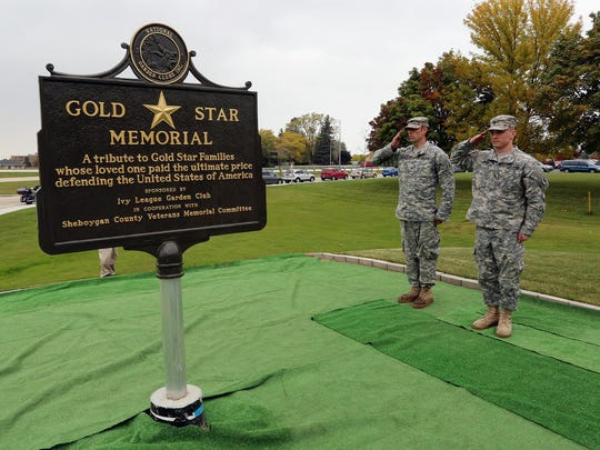 Two soldiers salute the newly dedicated Gold Star Memorial