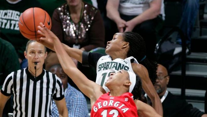 Michigan State's Morgan Green, top, and Georgia's Haley Clark (12) reach for a rebound Wednesday,  in East Lansing.