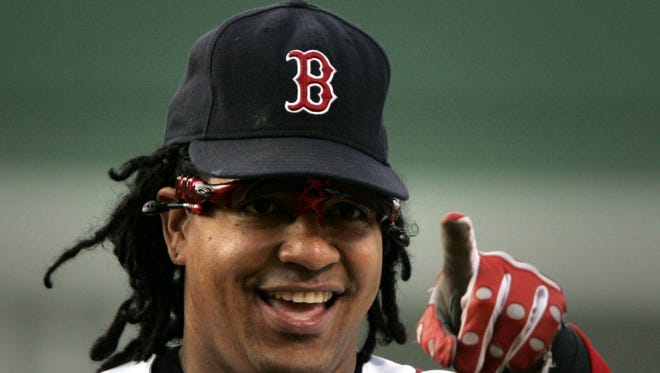 Boston Red Sox left fielder Manny Ramirez points to the fans while arriving on the field shortly before a game against the Minnesota Twins at Fenway Park in Boston, July 29, 2005.
