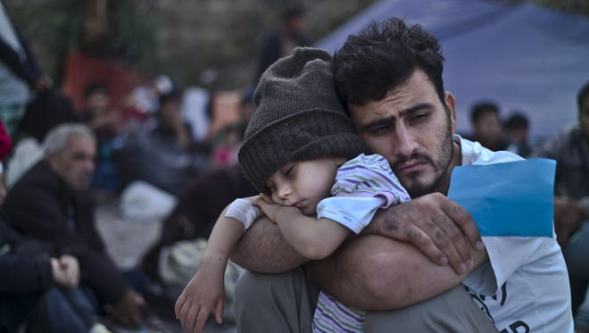 AP A Syrian refugee child sleeps in his father's arms Oct. 4 while waiting to board a bus after arriving on a dinghy from the Turkish coast to the northeastern Greek island of Lesbos. Pennsylvania Gov. Tom Wolf said the state would not turn its back on Syrian refugees.