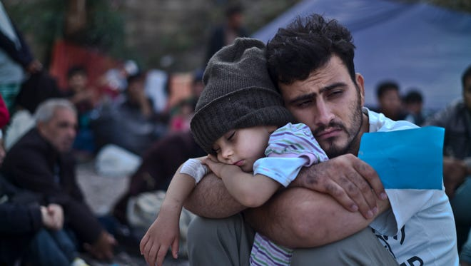 In this Sunday, Oct. 4, 2015 file photo, a Syrian refugee child sleeps in his father's arms while waiting at a resting point to board a bus, after arriving on a dinghy from the Turkish coast to the northeastern Greek island of Lesbos.