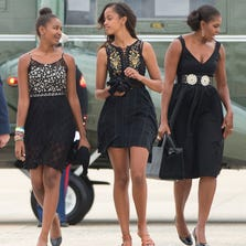 First lady Michelle Obama, right, and her daughters Sasha, left, and Malia, walk across the tarmac before boarding Air Force One prior to their departure from Andrews Air Force Base, Saturday. The first family is traveling to Westchester County, NY., to attend the wedding ceremony of White House chef Sam Kass and MSNBC host Alex Wagner.