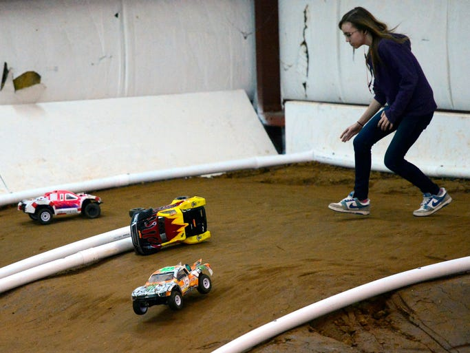 Allison Stoltz runs to right an overturned car during a race. Adventure RC Raceway celebrates opening day of it's indoor car track, as more than 100 compete on Saturday afternoon. March 22, 2014