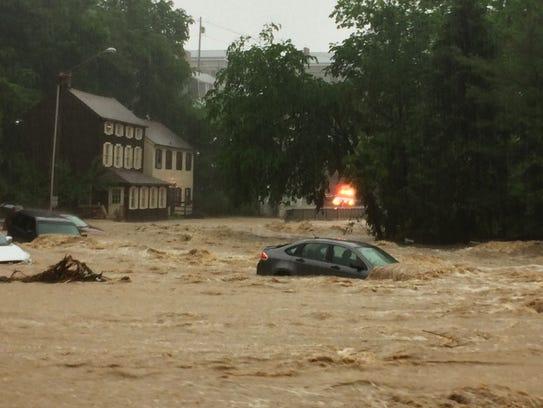 Water rushes through Main Street in Ellicott City,