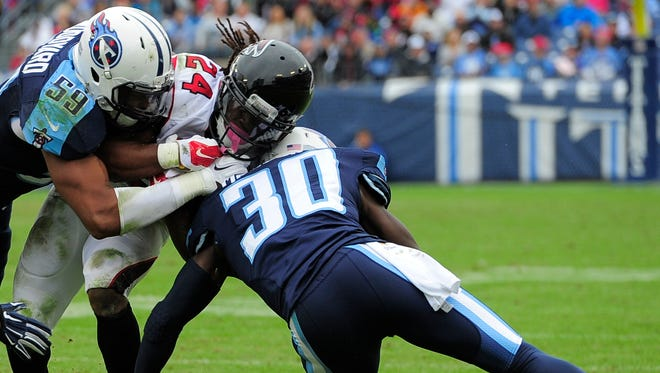 Titans inside linebacker Wesley Woodyard (59) and cornerback Jason McCourty (30) tackle Falcons running back Devonta Freeman (24) in the second quarter.