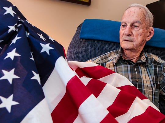 Inside his home at Stones River Manor, Wiley Herrod sits with a flag that flew in his honor at the Healing Field.