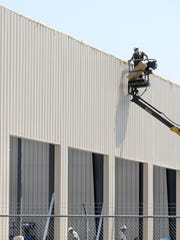 Construction crews work on the exterior trim of the