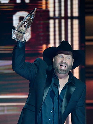Garth Brooks hoists his Entertainer of the Year award