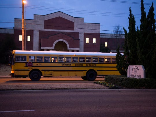 A bus passes Houston High School before dawn.