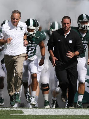 Michigan State Spartans head coach Mark Dantonio and injured Riley Bullough lead the team onto the field before the game against the Wisconsin Badgers on Saturday, Sept. 24, 2016 at Spartan Stadium.