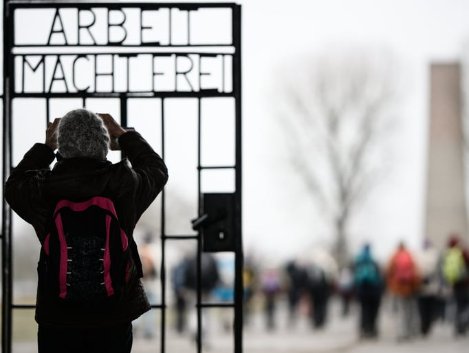 A visitor takes a photo of the words 'Arbeit macht