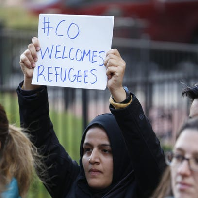 Nadeen Ibrahim, of Denver, waves a sign during a press conference Friday, Nov. 20, 2015, in Denver, where community leaders are asking that Syrian refugees be allowed in the United States in accordance with the strict vetting process that is already in place. (AP Photo/David Zalubowski)