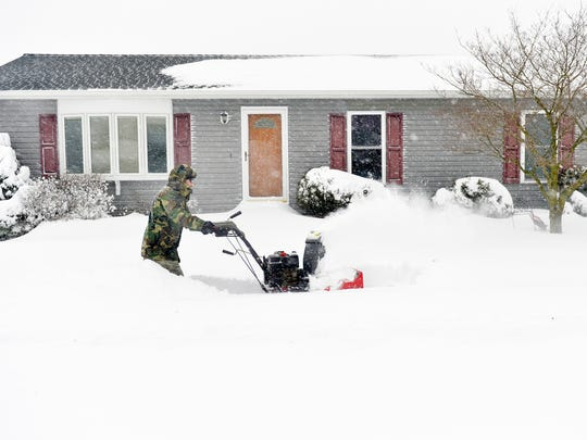 Keith Kittler of Hallam uses his snowblower to clear the sidewalk outside his neighbors' homes Saturday, Jan. 23, 2016. Kittler said he normally wouldn't attempt snowblowing until after a storm has concluded, but decided to create a pathway in case anyone needed a generator. A snow storm affecting much of the East Coast is expected to bring up to 3 feet of snow to York County, Pa., through Saturday evening.