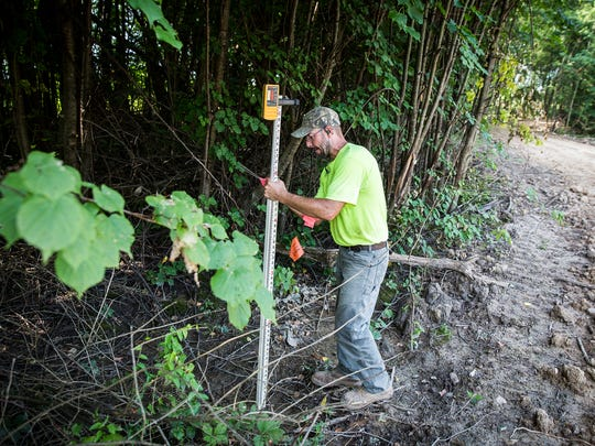 Allen Byler measures a section of the possible future site of a trail at the Red Tail Conservancy site off of Kilgore Avenue near the BorgWarner plant Tuesday morning.