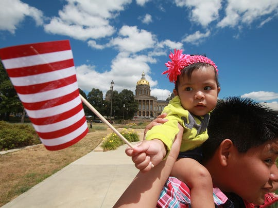 Eleven-month-old Alexa Gonzalez of Marshalltown holds a flag during a 2013 immigration reform rally at the Capitol in Des Moines.