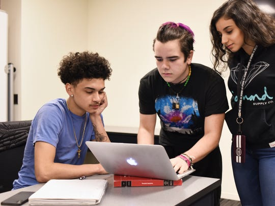 From left.  Sexton junior Scott Sutton, and  Lansing Eastern students Coby Castillo and Emma Asaf, both juniors, put the finishing touches on a presentation they practiced Tuesday, March 20, 2018, that they'll present to classmates about their semester-long insurance class at the Accident Fund in Lansing.