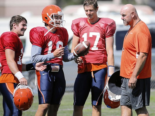 UTEP head coach Sean Kugler jokes with quarterbacks Mack Leftwich, left, Hunter McEachern, center, and Garrett Simpson during practice at Camp Ruidoso.