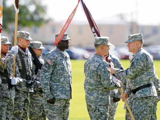 Maj. Gen. Thomas R. Tempel, Jr., right, passes the unit flag to new Beaumont Army Medical Center commander Col. John A. Smyrski III during a change of command ceremony at the Noel parade field on Fort Bliss Friday.