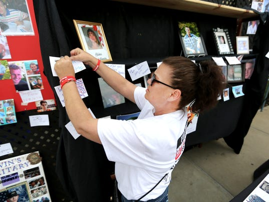 Kimberly  Wright of Northern Kentucky puts a note to a loved one on a board memorializing victims of heroin overdose.
