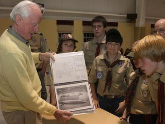 Ralph Jeffers shows local Boy Scouts his meticulously kept Pearl Harbor scrapbook.