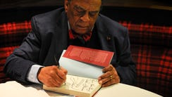 Ambassador Andrew Young signs a copy of his book for