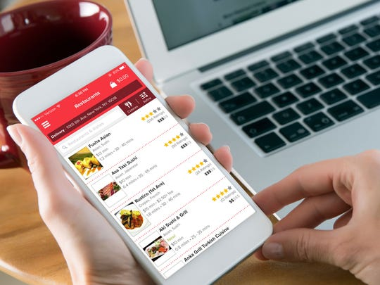 A person holds a phone with the Grubhub app open