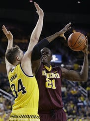 Minnesota center Bakary Konate (21) is defended by