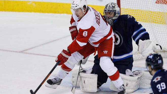 Red Wings forward Justin Abdelkader (8) deflects the puck past Jets goaltender Ondrej Pavelec for the tying goal.