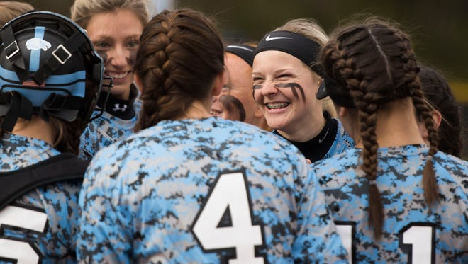 Senior outfielder Kayley Kern smiles while huddling with teammates. Kern batted .408 and contributed 48 RBIs in last year's championship season.
