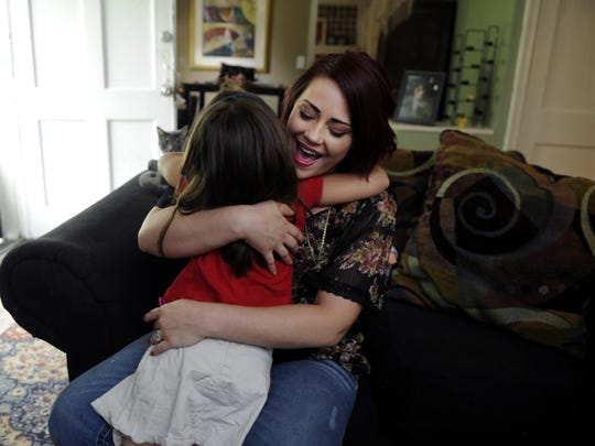 Shannon Casteel is a recovered opiates addict who went through Renewal House treatment. She get a hug from one of her daughters after returning home from school.