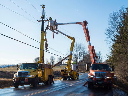 Crews work to erect a utility pole on a closed section