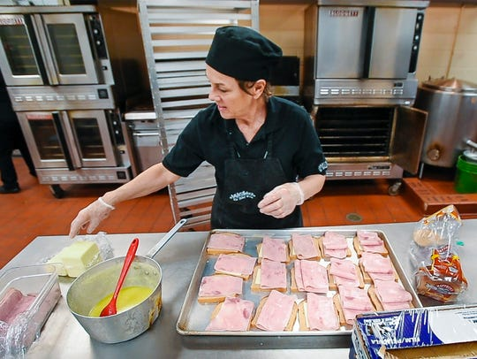Lead cook Martha Cary makes sandwiches during lunchtime