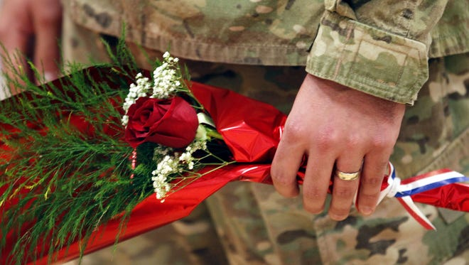 A member of the 833rd holds a rose during a homecoming ceremony November 23 in Ottumwa.