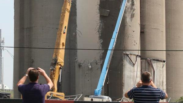 Onlookers stop and take photos of former Solae silos as they are demolished at UofL. July 31, 2014