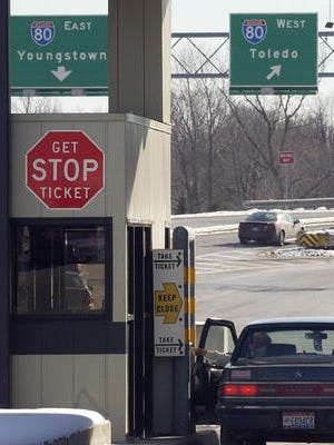 In this Jan. 21, 2005 file photo, a woman reaches for her ticket from a toll booth on the Ohio Turnpike in Strongsville, Ohio.