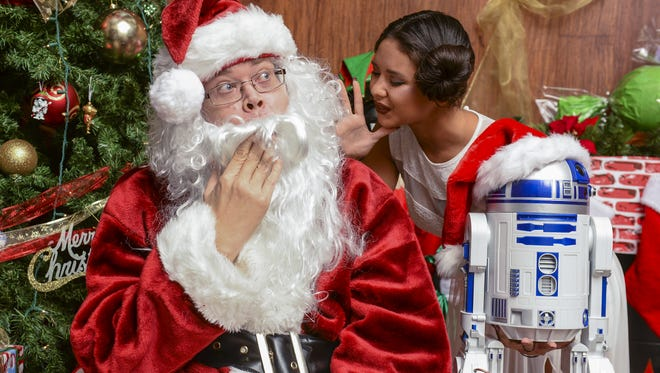 Santa Claus, left, portrayed by Pacific Daily News' Duane M. George, is caught off guard when he hears what Natalie Bejado, dressed as Star Wars' Princess Leia, wishes to find under her Christmas tree, during a photo shoot in Hagatna on Tuesday, Dec. 15.