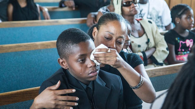Sharon Lamb and her son, Kasai Hayden, 10, extended family of Michelle Cusseaux, mourn their loss during funeral services for Cusseaux, a mentally ill woman who was slain by Phoenix police.