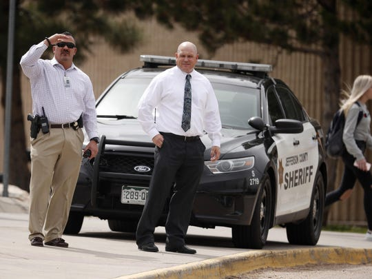 Columbine High School principal Scott Christy, right, joins an officer in watching as students leave the school late Tuesday, April 16, 2019, in Littleton, Colo. Following a lockdown.