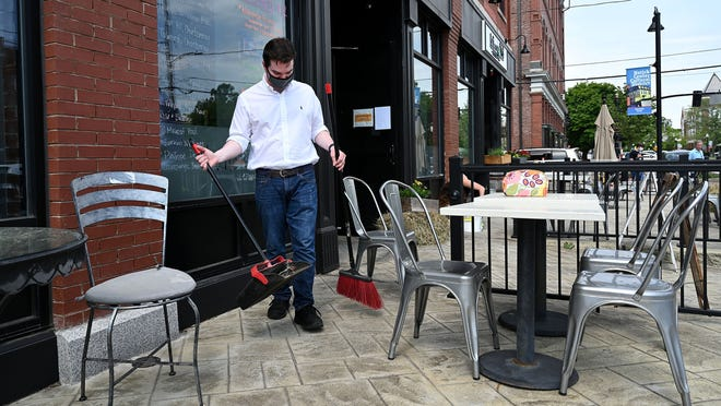 Scott Cornell, a server at Buttercup, a restaurant and bar in downtown Natick, sweeps the patio in preparation for opening up  to outdoor dining Tuesday afternoon. The restaurant is closed on Mondays, making Tuesday opening day after Gov. Charlie Baker announced that outdoor dining would be part of the second phase of the state´s plan to reopen of the economy. The 6:00 p.m. and 7:30 p.m. seatings are already fully booked this week, according to co-owner  Dora Tavel-Sanchez Luz.  [Daily News and Wicked Local Staff Photo/Ken McGagh