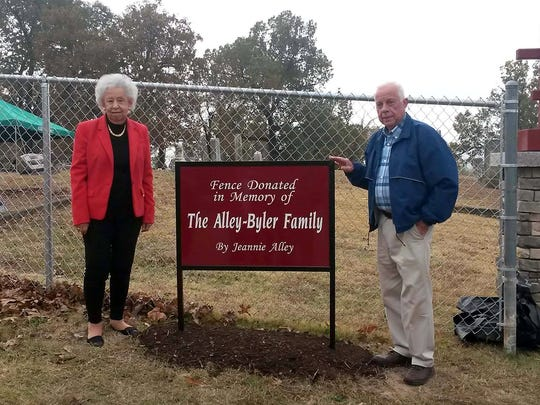 Jeannie Alley (left) and Mountain Home Mayor Joe Dillard are shown with a sign recognizing Alley's donation to provide new fencing at the Mountain Home Cemetery.