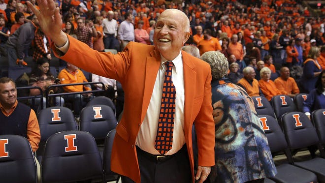 Retired Illinois coach Lou Henson waves to students in the orange crush section before a game against Notre Dame on Dec. 2, 2015, in Champaign.